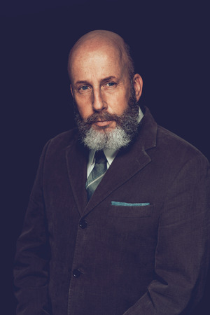 unemotional: Close up Portrait of an Adult Bald Man with Beard and Mustache, Wearing Formal Attire, Looking at the Camera. Isolated on a Black Background.