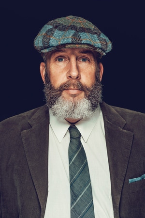 Close up Portrait of a Senior Man with Beard and Mustache, Wearing a Formal Attire with Ivy Cap, Looking at the Camera. Isolated on White Background. Stock Photo