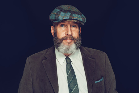 dapper: Stylish attractive bearded man in a cloth cap and suit looking at the camera with a quiet smile, on a black background