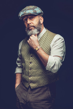 musing: Portrait of a Serious Adult Man in Green Formal Wear Posing on a Black Background with One Hand on his Hairy Chin While Looking at the Camera. Stock Photo