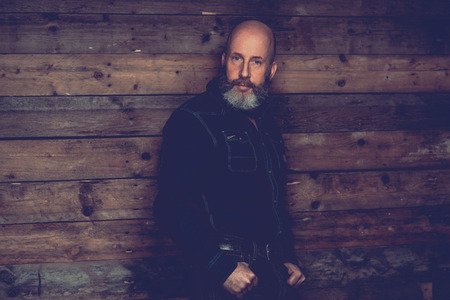 goatee: Adult Bald Goatee Man in Black Trendy Outfit Posing In front a Wooden Wall Background While Looking at the Camera.