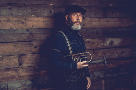 speculate: Adult Goatee Man in Black Fashionable Outfit with Ivy Cap Holding Trumpet In Front a Wooden Wall While Looking at the Camera.