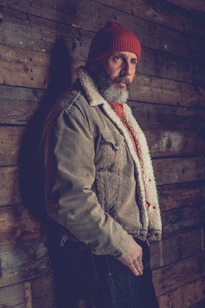 introspective: Close up Serious Male Goatee Senior in Fuzzy Jacket with Red Hat Leaning on Rustic Wooden Wall While Looking Afar.
