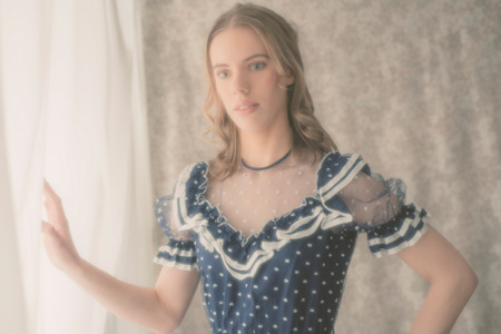 olden day: Faded aged portrait of a pretty blond girl in vintage fashion standing with her hand to a filmy white curtain looking at the camera with a serious expression