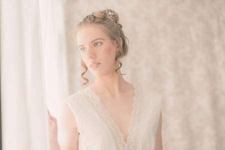 Close up Elegant Young Woman in White Dress Viewing Outside From the Window in her Room with White Curtain.