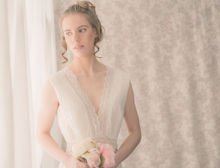 Close up Half Body Shot of an Elegant Young Woman in White Lace Dress, Holding Fresh Rose Flowers, Standing Beside the Window with Curtains While Looking Outside. Stock Photo