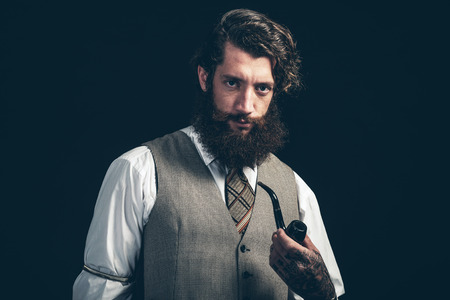 bushy: Stylish man with a bushy beard in retro fashion standing smoking a pipe looking at the camera with a serious expression Stock Photo