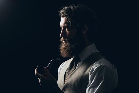 喫煙パイプ中を左に見てフレームの黒の背景にシルエットの長い鬚ひげ保持おとこを閉じます。 写真素材