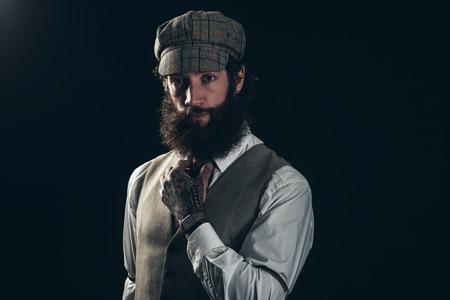 jaunty: Close up estilo magn�fico Hombre joven con la barba larga, vestido con traje formal con Gorra, Sosteniendo su corbata mientras mira a la c�mara. Aislado en Negro.