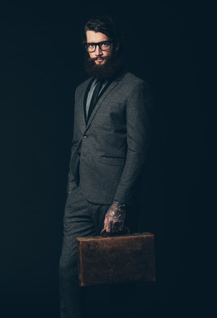 goatee: Portrait of a Young Businessman with Long Goatee, Wearing Elegant Formal Wear With Eyeglasses, Holding his Briefcase and Looking at the Camera. Isolated on Black Background.