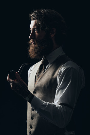 sombre: Half Body Shot of an Elegant Young Guy with Facial Hair, Wearing Formal Wear, Holding a Smoking Pipe While Looking to the Left of the Frame Seriously. Stock Photo