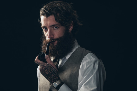 Close up Portrait of a Handsome Young Man, with Tattoo on his Hand, Smoking Using a Tobacco Pipe While Looking at the Camera. Isolated on Black Background.