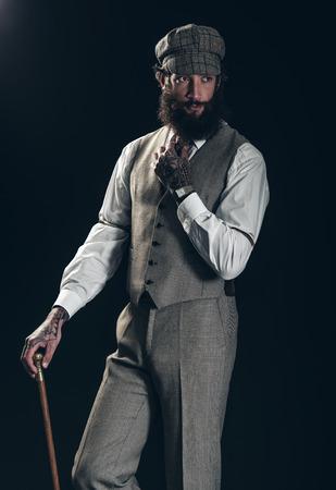 jaunty: Dapper caballero a la antigua con una barba espesa que llevaba una gorra de tela y el chaleco y llevando un bast�n sobre un fondo oscuro Foto de archivo