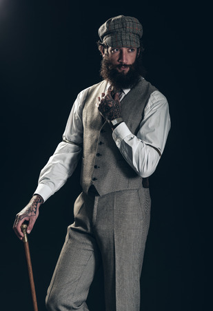 dapper: Dapper old-fashioned gentleman with a bushy beard wearing a cloth cap and waistcoat and carrying a cane over a dark background Stock Photo