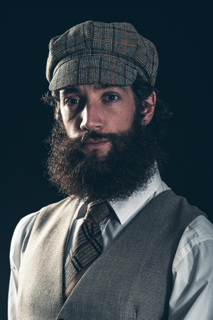 jaunty: Attractive bearded man in vintage fashion wearing a cloth peaked cap and waistcoat looking at the camera with an enigmatic smile, dark background Stock Photo