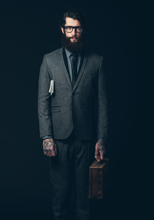 tattoo arm: Portrait of a Young Businessman with long Goatee Beard, Standing in Formal Suit with Eyeglasses, Holding a Briefcase While Looking at the Camera. Isolated on Black Background.