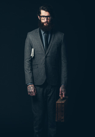 inscrutable: Portrait of a Serious Bearded Young Businessman in Formal Wear Holding his Briefcase with Newspaper on his Armpit While Looking at the Camera. Isolated on Black Background.