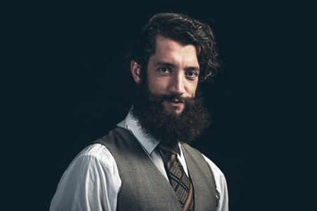 bushy: Attractive businessman with a bushy beard wearing a waistcoat looking at the camera with a smile over a dark background, close up head and shoulders