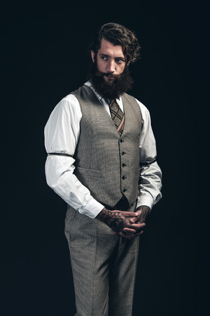 watchful: Thoughtful stylish bearded businessman standing clasping his hands in front of him looking to the side with a watchful expression, hands have tattoos, over a dark background