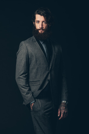 nonchalant: Portrait of a Young Handsome Man with Long Beard, Wearing an Elegant Formal Suit, Looking at Camera on a Black Background. Stock Photo