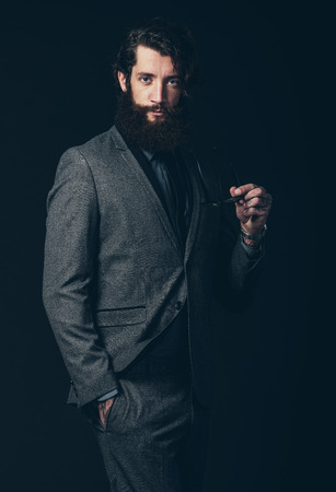 inscrutable: Portrait of a Gorgeous Young Man with Long Facial Hair, Wearing Elegant Formal Fashion, Holding his Eyeglasses While Looking at the Camera. Isolated on Black. Stock Photo