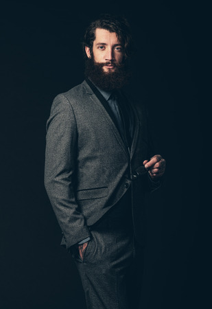 eye wear: Portrait of an Attractive Young Guy with Beard and Mustache, Wearing Classy Formal Suit, Holding his Eye Wear with the Other Hand in his Pocket. Isolated on Black.