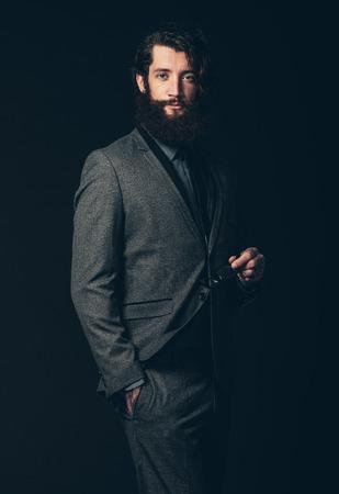 eye wear: Retrato de una atractiva joven con barba y bigote, vestido con traje formal con clase, sosteniendo sus ojos Use con la otra mano en su bolsillo. Aislado en Negro.