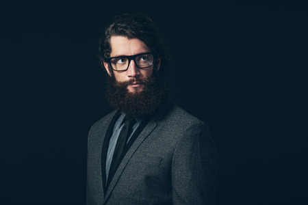 goatee: Close up Gorgeous Young Man with Long Goatee Beard, Wearing Formal Fashion with Eyeglasses, Looking to the Upper Right of the Frame on a Black Background.