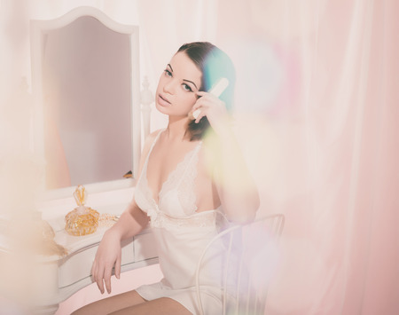 Sexy Young Woman Sitting at her Room While Combing her Hair Behind a Sequins Curtain and Looking at the Camera. Stock Photo
