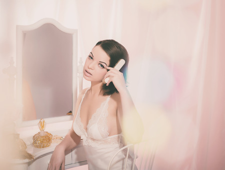 Sexy Young Girl Wearing White Nightdress Combing her Black Hair While Sitting on a Chair at her Room.