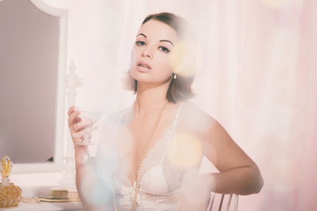 tantalizing: Close up Seductive Young Woman in White Nightie Holding a Glass of Drink Behind a Beaded Shower Curtain While Looking at the Camera.