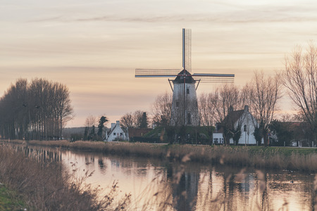 Windmill and farm houses alongside a canal mirrored in the calm water at dusk or dawn as a feint pink tinges the sky in a scenic landscape photo