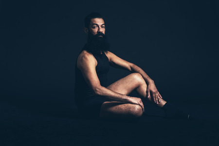 goatee: Portrait of an Athletic Man with Long Goatee Beard Sitting on the Floor While Looking at the Camera on a Black Background. Stock Photo