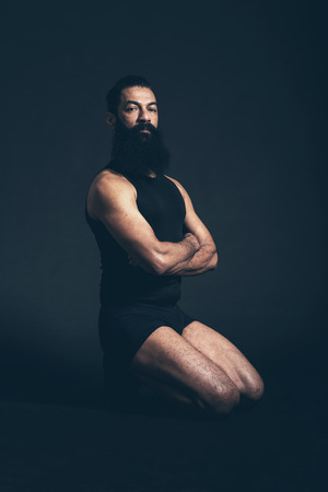 expressionless: Portrait of a Confident Athletic Man Kneeling on the Floor While Sitting on his Ankles with Arms Crossed and Looking at the Camera Seriously. Captured in Studio with Black Background. Stock Photo