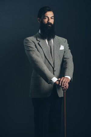 dapper: Portrait of a Serious Man with Long Goatee Beard Wearing Formal Wear While Holding Cane on a Black Background. Stock Photo