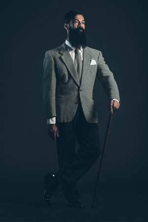 jaunty: Full Length Shot of a Man with Long Beard Wearing Formal Suit Standing in Crossed Legs and Holding Cane While Looking to the Right of the Frame on a Black Background. Stock Photo