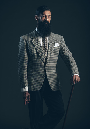 inscrutable: Serious Man with Long Facial Hair Posing in Formal Suit While Holding a Walking Cane and Looking at the Camera on a Black Background.