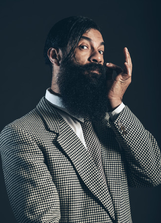 Handsome gentleman with a big bushy beard tweaking his mustache while giving the camera a supercilious look