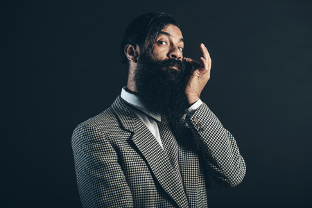 supercilious: Man with Long Beard and Mustache, Wearing Checkered Formal Coat, Touching his Face While Looking at Camera on a Black Background.