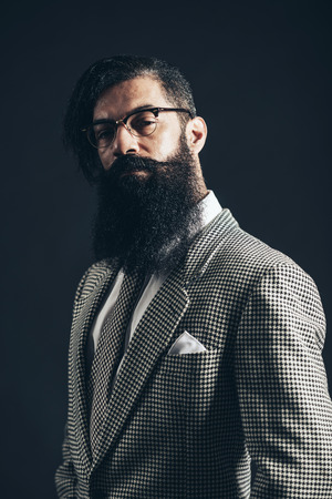 quizzical: Close up Portrait of a Young Man with Long Facial Hair Wearing Formal Suit with Eyeglasses Looking at Camera Seriously on a Black Background Stock Photo
