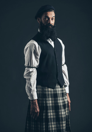 Attractive bearded man wearing a plaid Scottish kilt and waistcoat standing looking at the camera wuith a serious expression over a dark background photo