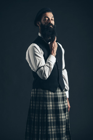 checkered skirt: Stylish Man, Wearing Formal Wear Paired with Checkered Skirt, Holding his Long Goatee Beard While Looking at the Camera on Black Background.