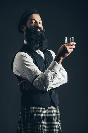 supercilious: Scottish gentleman wearing a plaid kilt enjoying a glass of whiskey standing with crossed arms giving the camera a supercilious look Stock Photo