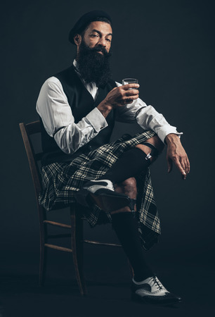 legs crossed: Stylish Bearded Young Guy with Long Facial Hair Sitting on a Single Chair with Legs Crossed Holding a Glass of Drink While Looking at the Camera on Black Background. Stock Photo