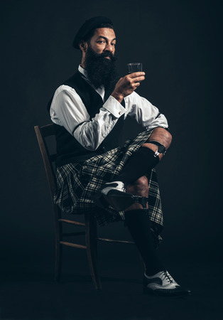 nightcap: Bearded Scotsman enjoying a nightcap sitting in a chair in his kilt in the darkness holding a glass of whiskey or brandy