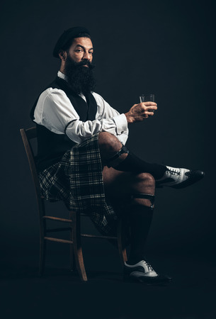 crossing legs: Serious Bearded Man Wearing Fashionable Attire Sitting on a Chair and Crossing Legs While Holding a Glass of Wine While Looking at the Camera. Captured in Studio on Black Background.