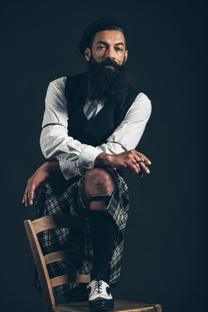 Serious thoughtful bearded Scotsman in a kilt standing with one foot up on a chair smoking a cigarette over a dark background Stock Photo