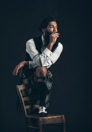 crossed cigarette: Thoughtful Scotsman with a bushy beard wearing his plaid kilt standing with one foot on a chair smoking and staring off into the distance