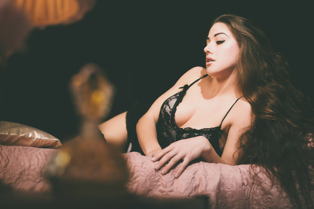 Seductive Young Woman Wearing Sexy Black Lace Lingerie Lying on her Side on a Bed While Looking Down. Captured at the Bedroom with Black Background. Фото со стока