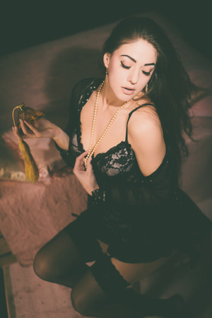 nightwear: Gorgeous Young Woman in Black Nightwear Posing at her Bedroom Seductively While Holding a Bottle of Perfume.
